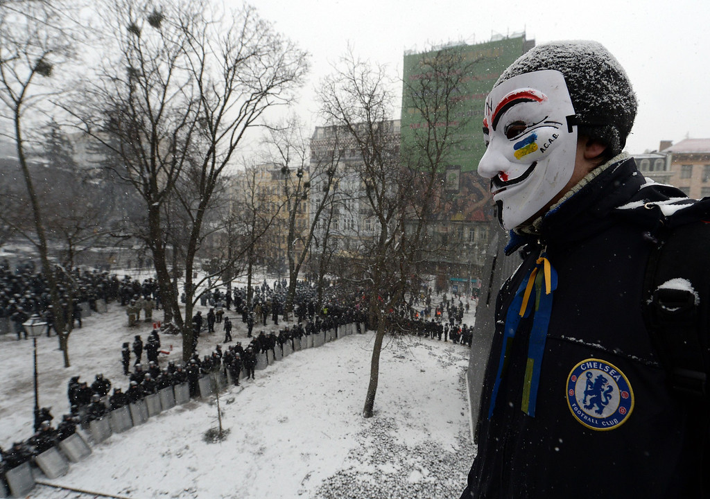 . An Ukrainian opposition activist wearing a Guy Fawkes mask looks at anti-riot forces blocking the access to the parliament in Kiev on January 21, 2014. After a night of violence, a temporary truce appeared to be in place with the protesters no longer launching the Molotov cocktails and stones that had marked their action since the clashes erupted on the night of January 19. AFP PHOTO/ SERGEI SUPINSKY/AFP/Getty Images