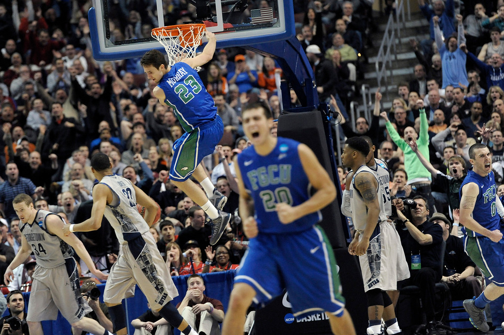 . Florida Gulf Coast\'s Eddie Murray (23) hangs from the rim after a dunk as Chase Fieler (20) and Brett Comer (0) celebrate during the second half of a second-round game against Georgetown in the NCAA college basketball tournament on Friday, March 22, 2013, in Philadelphia. (AP Photo/Michael Perez)