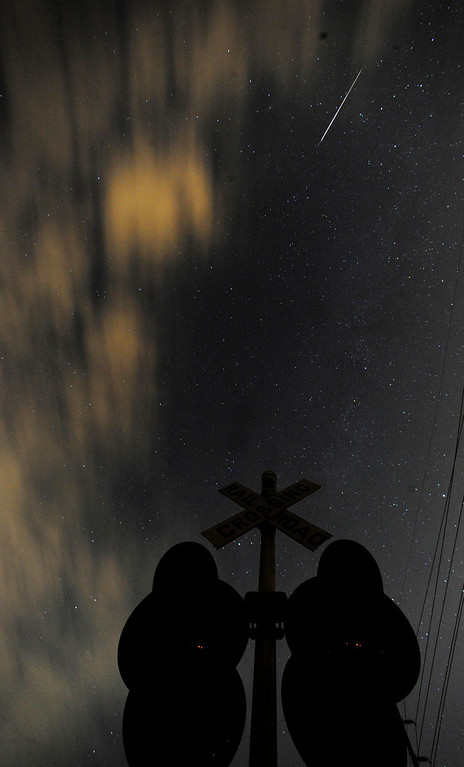 . A meteor is seen over a railroad crossing at Ditto Marina Parkway, early Monday, Aug. 12, 2013, in Huntsville, Ala. (AP Photo/AL.com, Eric Schultz)