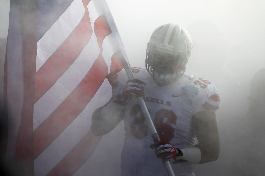 . DALLAS, TX - JANUARY 01: Alex Klorman #36 of the UNLV Rebels walks through the tunnel holding an American flag before the Heart of Dallas Bowl against the North Texas Mean Green at Cotton Bowl Stadium on January 1, 2014 in Dallas, Texas.  (Photo by Sarah Glenn/Getty Images)