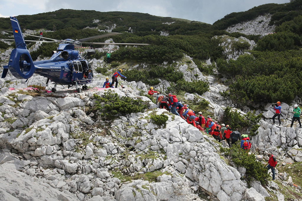 . In this handout photo provided by the Bavarian Mountain Patrol (Bergwacht Bayern), rescue workers carry injured spelunker Johann Westhauser to a waiting helicopter after they brought him to the surface from the Riesending vertical cave during the final phase of his rescue on June 19, 2014 near Marktschellenberg, Germany. (Photo by Bergwacht Bayern via Getty Images)