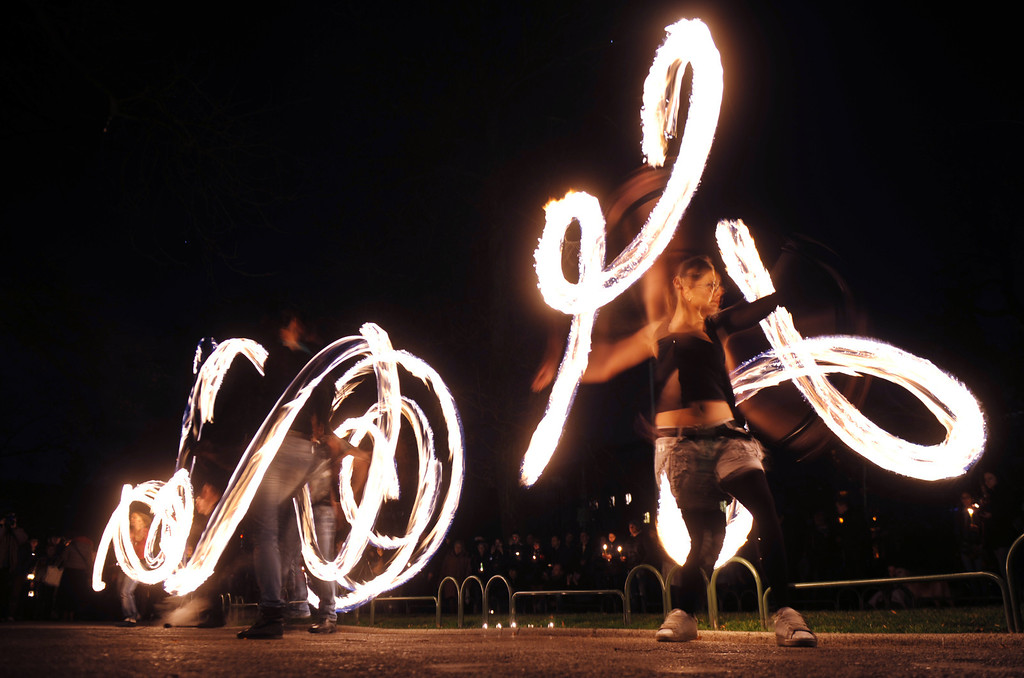 . A fire acrobats performs in front of the Bulgarian National Theatre, with lights turned off as part of the Earth Hour in Sofia on March 23, 2013. Millions of people were expected to switch off their lights for Earth Hour on March 23 in a global effort to raise awareness about climate change that was even to be monitored from space.. NIKOLAY DOYCHINOV/AFP/Getty Images