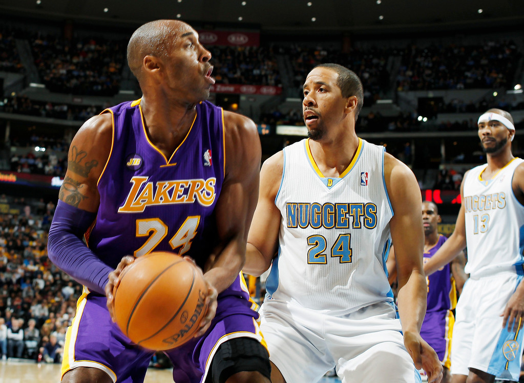 . Los Angeles Lakers guard Kobe Bryant, left, looks for a shot as Denver Nuggets guard Andre Miller covers in the first quarter of an NBA basketball game in Denver on Monday, Feb. 25, 2013. (AP Photo/David Zalubowski)