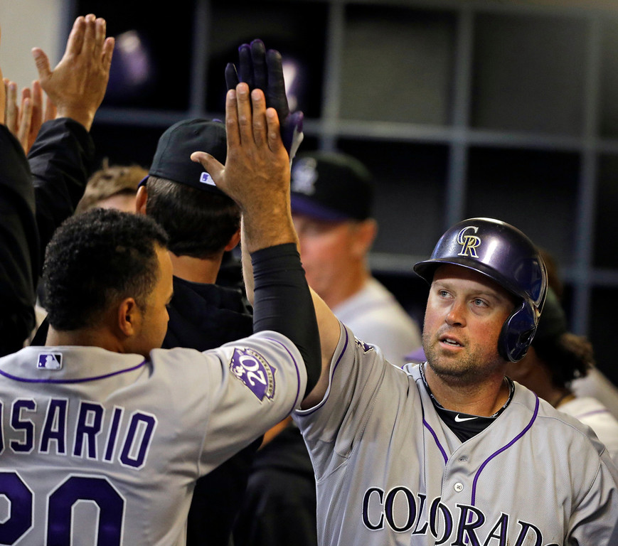 . Colorado Rockies\' Michael Cuddyer, right, gets a high-five from Wilin Rosario after his two-run home run during the ninth inning of a baseball game, Wednesday, April 3, 2013, in Milwaukee. (AP Photo/Jeffrey Phelps)