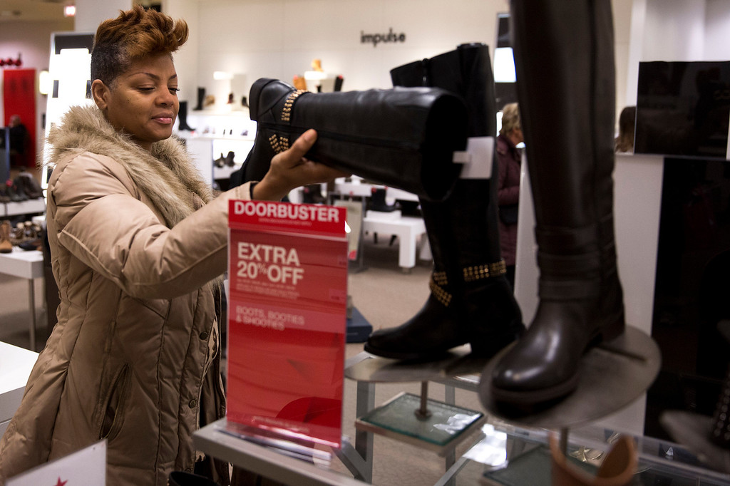 . Deb Cuzan of Chicago looks at boots while shopping during Black Friday at Macy\'s on Friday, Nov. 29, 2013, in Chicago. Black Friday, the day after Thanksgiving, is typically the nation\'s biggest shopping day of the year.  (AP Photo/Andrew A. Nelles)