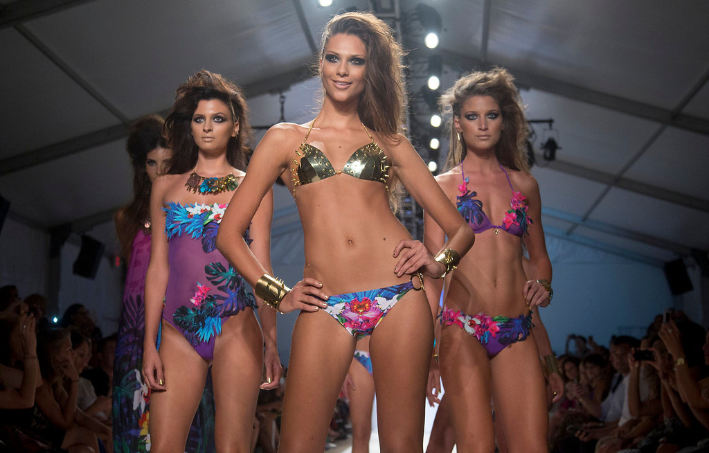 . In this Friday, July 19, 2013 photo, a models walk the runway during the Dolores Cortes show at the Mercedes-Benz Fashion Week Swim show in Miami Beach, Fla. (AP Photo/J Pat Carter)