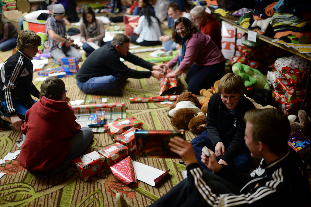 """. DENVER, CO. DECEMBER 21: The annual Father Woody Christmas Party in Denver, Colorado December 21, 2013. In advance of handing out 5,000 gifts, volunteers are doing a \""""wrapping party\"""" at the Sheraton Denver Downtown Hotel. (Photo by Hyoung Chang/The Denver Post)"""