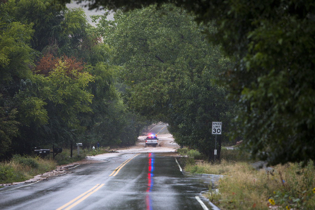 . BOULDER, CO - SEPTEMBER 12:  A police truck speeds up Linden Drive September 12, 2013 in Boulder, Colorado. An estimated 6-10 inches of rain fell in 12-18 hours and more is expected throughout the day. Flash flood sirens warned people to stay away from Boulder Creek and seek higher ground.  (Photo by Dana Romanoff/Getty Images)