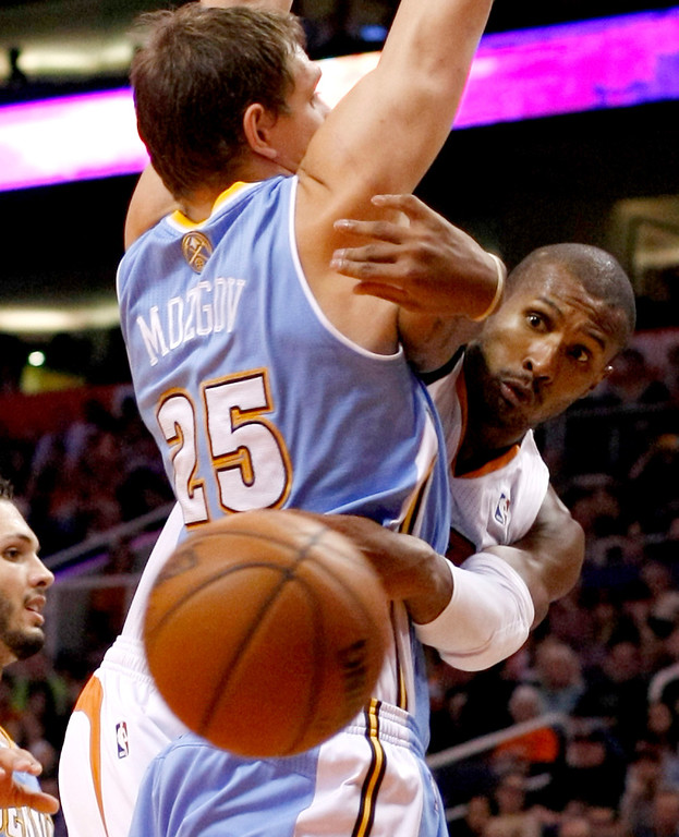 . Phoenix Suns shooting guard Leandro Barbosa, right, makes the pass around Denver Nuggets center Timofey Mozgov (25) in the third quarter of an NBA basketball game, Sunday, Jan. 19, 2014, in Phoenix. (AP Photo/Rick Scuteri)