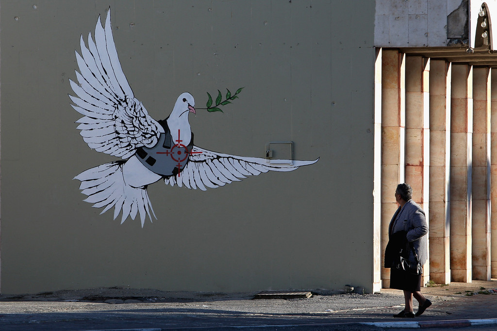 . BETHLEHEM, WEST BANK - DECEMBER 05:  A Palestinian woman pauses to look at a wall painting by elusive British graffiti artist Banksy December 5, 2007 on a shop wall in the biblical city of Bethlehem in the West Bank. The Bristol-born artist has adorned Israel\'s West Bank separation barrier and Bethlehem walls with new images, including this one of a dove wearing a flak jacket and a soldier being frisked by a young girl. His works, along with those of other international artists, are part of an exhibition called Santa\'s Ghetto.  (Photo by David Silverman/Getty Images)