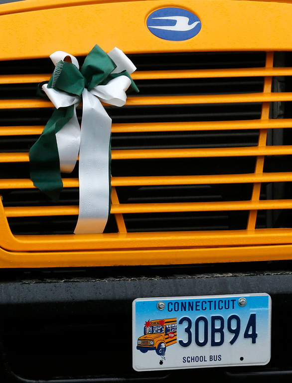 . A green and white memorial ribbon is attached to the grill of a school bus as it rolls through town in Newtown, Conn., Tuesday, Dec. 18, 2012. Classes resume Tuesday for Newtown schools except those at Sandy Hook. Buses ferrying students to schools were festooned with large green and white ribbons on the front grills, the colors of Sandy Hook. At Newtown High School, students in sweatshirts and jackets, many wearing headphones, betrayed mixed emotions.  Adam Lanza walked into Sandy Hook Elementary School in Newtown,  Friday and opened fire, killing 26 people, including 20 children, before killing himself.(AP Photo/Jason DeCrow)