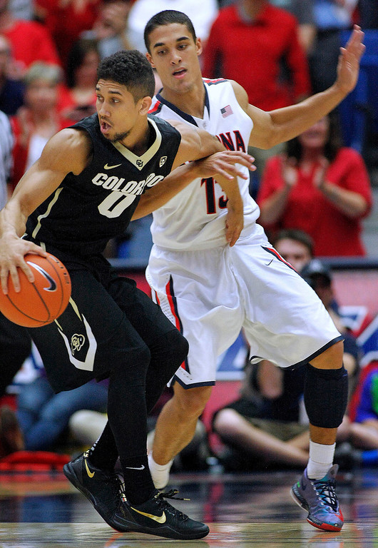 . Colorado\'s Askia Booker (0) barely gets away from the pressing defense of Arizona\'s Nick Johnson (13) in the first half of an NCAA college basketball game, Thursday, Jan. 23, 2014 in Tucson, Ariz. (AP Photo/John Miller)