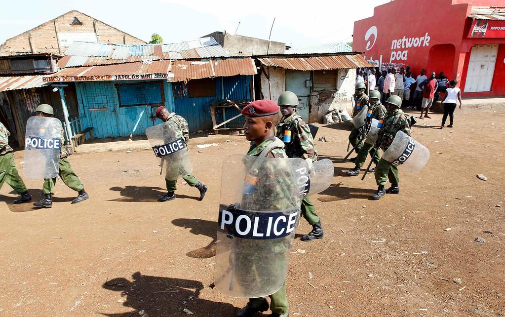 . Riot police walk past residents as tension arises after Uhuru Kenyatta was declared winner of Kenya\'s presidential election, in Nyallenda slums in Kenya\'s western town of Kisumu, 350km (218 miles) from the capital Nairobi, March 9, 2013. REUTERS/Thomas Mukoya