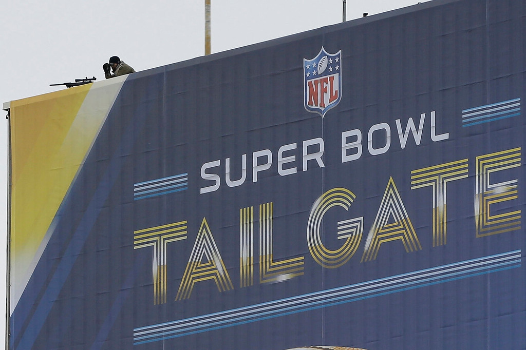 . A security officer works atop a Super Bowl sign at MetLife Stadium before the NFL Super Bowl XLVIII football game Sunday, Feb. 2, 2014, in East Rutherford, N.J. (AP Photo/Ben Margot)