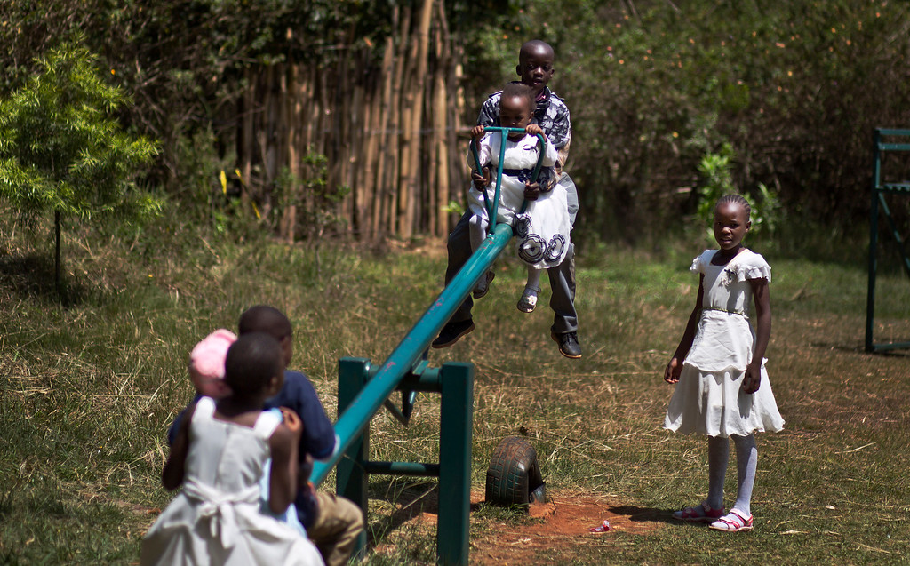 . Kenyan children whose families lost relatives in the attack play on a nearby seesaw while their parents attend a memorial service marking the one-month anniversary of the the Sept. 21 Westgate Mall terrorist attack, in Karura Forest in Nairobi, Kenya Monday, Oct. 21, 2013. (AP Photo/Ben Curtis)