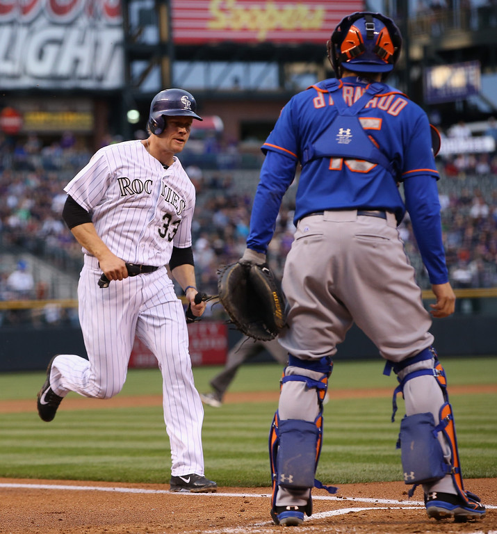. DENVER, CO - MAY 02:  Justin Morneau #33 of the Colorado Rockies scores on a sacrifice fly by Corey Dickerson #6 of the Colorado Rockies as catcher Travis d\'Arnaud #15 of the New York Mets looks on and the Rockies take a 4-1 lead in the first inning at Coors Field on May 2, 2014 in Denver, Colorado.  (Photo by Doug Pensinger/Getty Images)