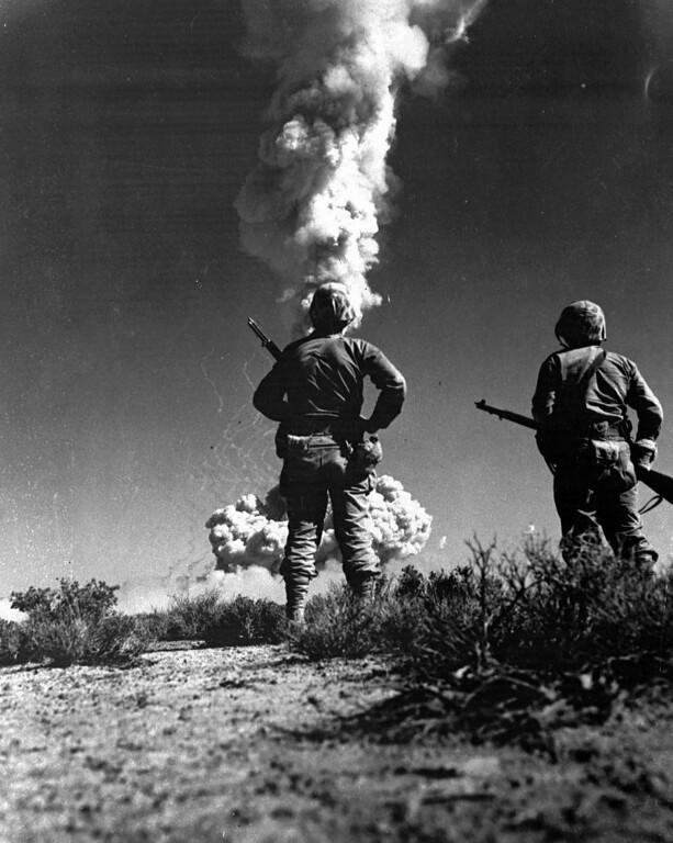 ". Two soldiers look at an atomic cloud during a nuclear bomb testing in Nevada in this 1952 file photo. Newly declassified Pentagon records show that troop exercises during nuclear bomb tests in the 1950s were designed to pursued soldiers their fear of radiation was irrational and to give them ""an emotional vaccination\"" to the blasts. It has been widely known for decades that soldiers were deliberately exposed to radiation during exercises starting in 1951 at the Nevada nuclear test range. The new documents open a window into the reasoning by military leaders in then-secret discussions about how far to go in using GI\'s in the tests. (AP Photo/files)"
