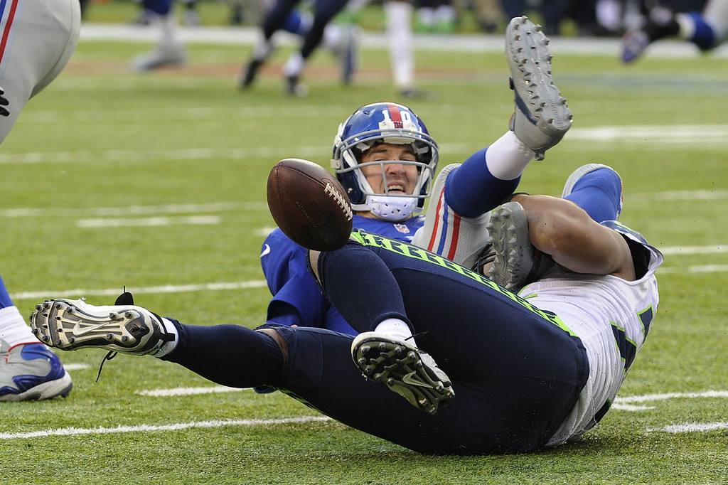 . Seattle Seahawks defensive end Michael Bennett, bottom, forces a fumble off New York Giants quarterback Eli Manning  during the second half of an NFL football game on Sunday, Dec. 15, 2013, in East Rutherford, N.J. The Giants recovered their fumble on the play. (AP Photo/Bill Kostroun)