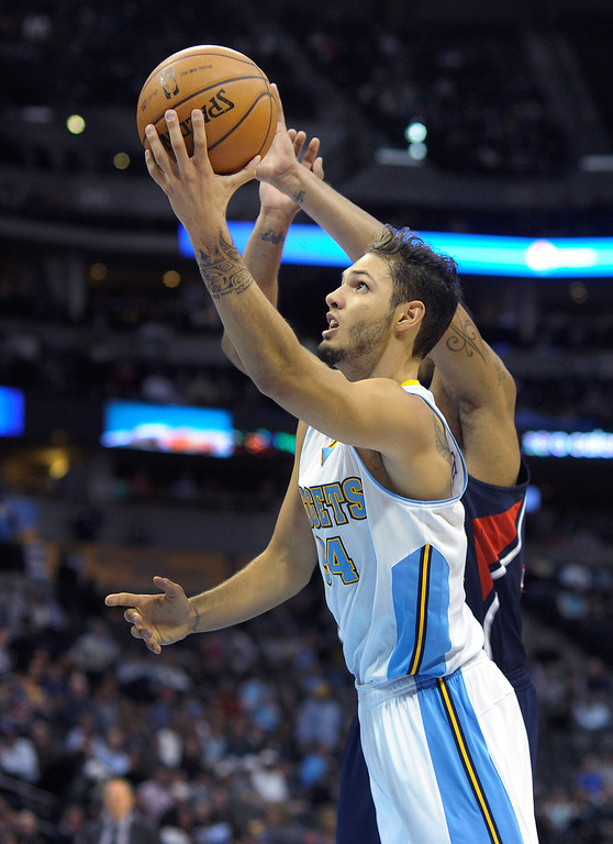 . Denver guard Evan Fournier flew past Atlanta defender Mike Scott in the first half.   Photo By Karl Gehring/The Denver Post