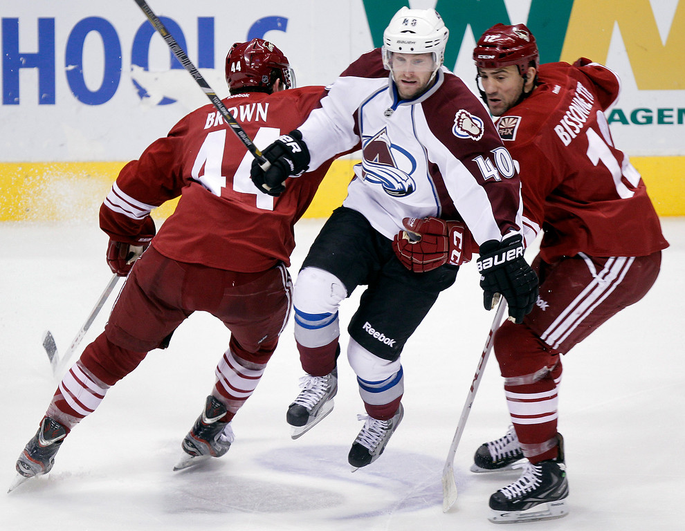 . Colorado Avalanche center Mark Oliver, center, leaps between Phoenix Coyotes center Chris Brown, left, and left winger Paul Bissonnette, right, in the third period of NHL hockey game Saturday, April 6, 2013, in Glendale, Ariz. The Coyotes won 4-0. (AP Photo/Paul Connors)