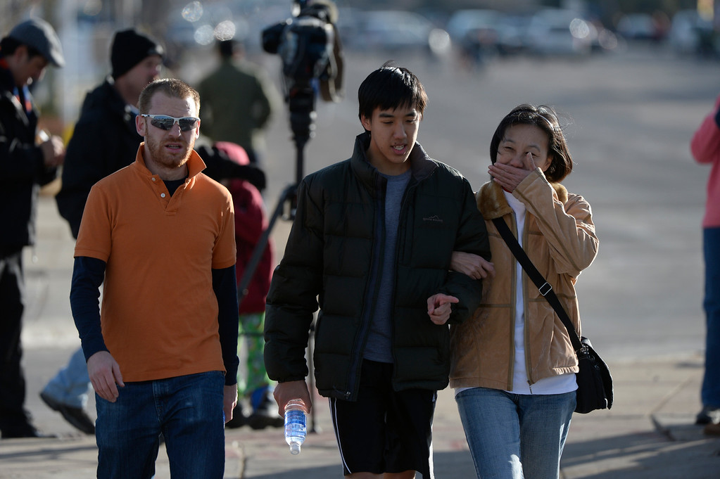 . CENTENNIAL, CO. - DECEMBER 13: William Hsin is reunited with his mother, Wang  at Arapahoe High School in Centennial, CO December 13, 2013. A student who carried a shotgun into Arapahoe High School and asked where to find a specific teacher opened fire on Friday, wounding two fellow students before apparently killing himself, Arapahoe County Sheriff Grayson Robinson said. William was in gym class and was instructed to hide in the weight room. (Photo By Craig F. Walker / The Denver Post)