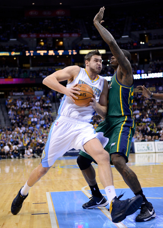 . Denver Nuggets forward Danilo Gallinari, left, from Italy, is fouled by Utah Jazz forward Marvin Williams, right, during the first quarter of an NBA basketball game on Saturday, Jan. 5, 2013, in Denver. (AP Photo/Jack Dempsey)