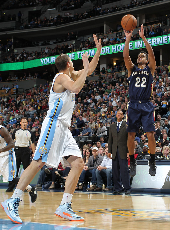 . New Orleans Pelicans guard Brian Roberts, right, takes a shot over Denver Nuggets center Timofey Mozgov, of Russia, in the third quarter of the Nuggets\' 102-93 victory in an NBA basketball game in Denver on Sunday, Dec. 15, 2013. (AP Photo/David Zalubowski)