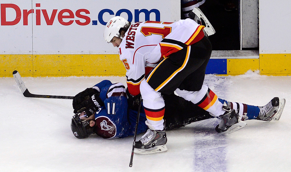 . Kevin Westgarth (15) of the Calgary Flames checks Jamie McGinn (11) of the Colorado Avalanche during the second period. Westgarth was called for unsportsmanlike conduct on the play.  (Photo by AAron Ontiveroz/The Denver Post)