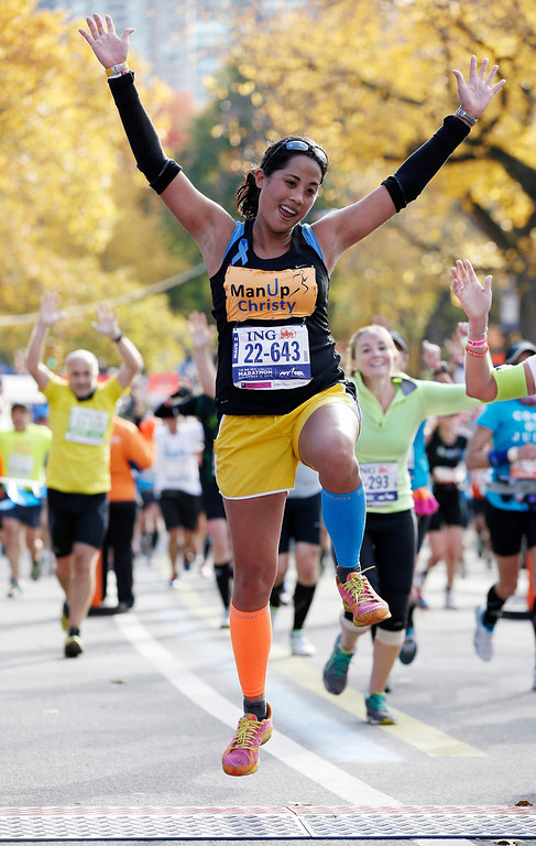 . Christy Pasion of New York leaps across the finish line after completing the New York City marathon, Sunday, Nov. 3, 2013, in New York. (AP Photo/Kathy Willens)