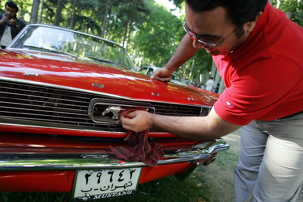 . An Iranian man cleans his 1965 Ford Mustang at a classic car show in Tehran, 29 May 2006.  HASSAN AMMAR/AFP/Getty Images