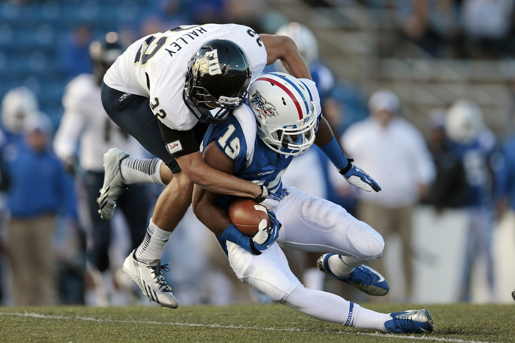 . Middle Tennessee wide receiver Marcus Henry (19) is brought down by Florida International safety Justin Halley (32) in the first half of an NCAA college football game on Saturday, Nov. 9, 2013, in Murfreesboro, Tenn. (AP Photo/Mark Humphrey)
