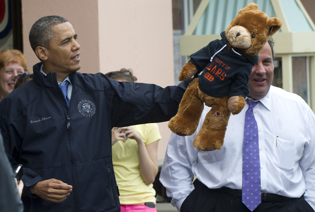 . US President Barack Obama holds a stuffed bear alongside New Jersey Governor Chris Christie after playing an arcade game along the boardwalk as they view rebuilding efforts following last year\'s Hurricane Sandy in Point Pleasant, New Jersey, on May 28, 2013.     AFP PHOTO / Saul LOEB/AFP/Getty Images