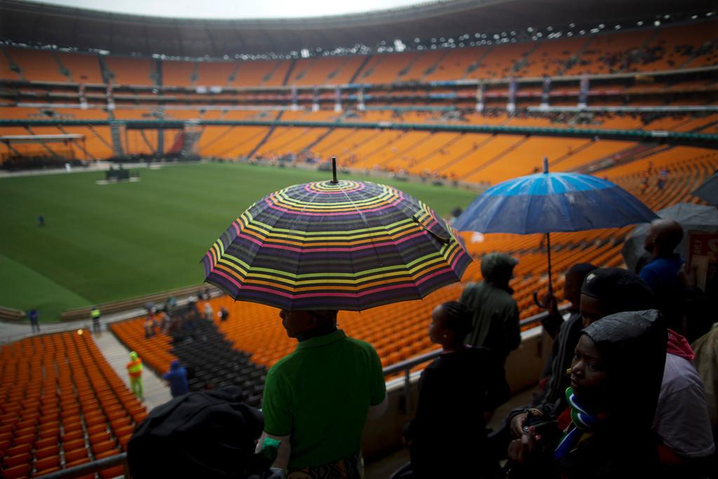 . Mourners wait for the memorial service for former South African president Nelson Mandela inside FNB Stadium in Soweto near Johannesburg, Tuesday, Dec. 10, 2013. (AP Photo/Muhammed Muheisen)
