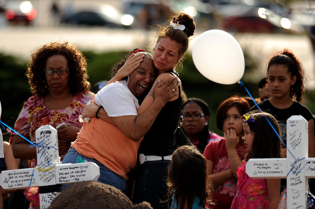 . People comfort each other at the memorial for shooting victims at the corner of E. Centerpoint Dr. and S. Sable Blvd. in Aurora, CO on Sunday, July 22, 2012. 12 cross are placed at the Memorial. Hyoung Chang, The Denver Post