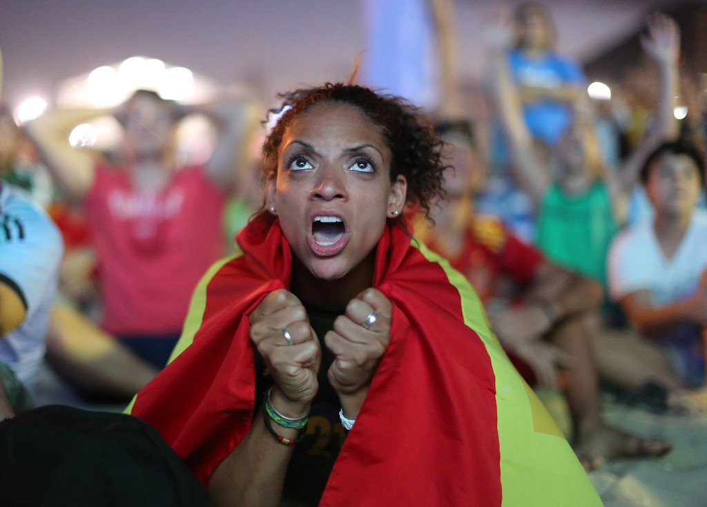 . Wrapped in a Spanish national flag, a soccer fan reacts in frustration as she watches the live broadcast of the World Cup match between Spain and the Netherlands inside the FIFA Fan Fest area on Copacabana beach in Rio de Janeiro, Brazil, Friday, June 13, 2014. The Netherlands thrashed Spain 5-1 Friday. It was a humiliating defeat for the defending World Cup champions. (AP Photo/Leo Correa)