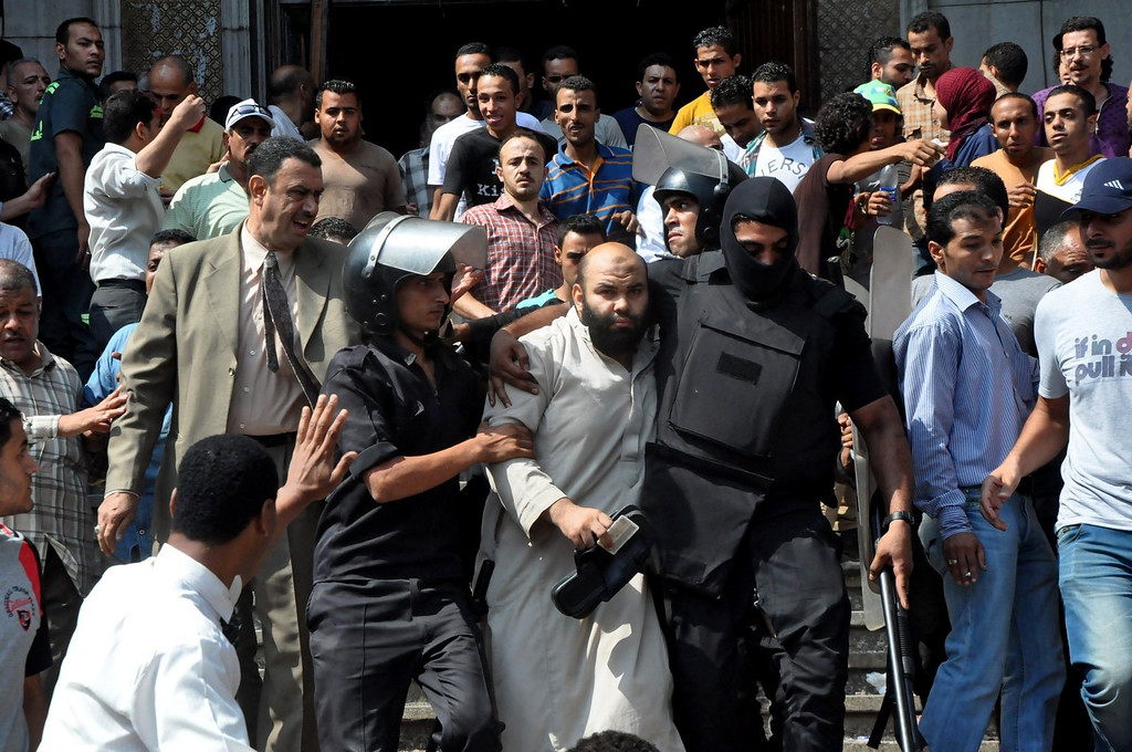 . Egyptians security forces escort an Islamist supporter of the Muslim Brotherhood out of the al-Fatah mosque, after hundreds of Islamist protesters barricaded themselves inside the mosque overnight, following a day of fierce street battles that left scores of people dead, near Ramses Square in downtown Cairo, Egypt, Saturday, Aug. 17, 2013. Authorities say police in Cairo are negotiating with people barricaded in a mosque and promising them safe passage if they leave. Muslim Brotherhood supporters of Egypt\'s ousted Islamist president are vowing to defy a state of emergency with new protests today, adding to the tension. (AP Photo/Hussein Tallal)