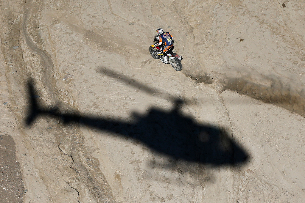 . The shadow of a helicopter is projected on the ground as Marc Coma of Spain rides his KTM motorcycle during the second stage of the Dakar Rally between the cities of San Luis and San Rafael in San Rafael, Argentina,  Monday, Jan. 6, 2014. The second stage is regarded as one of the fastest in the two-week rally, which ends Jan. 18 in Valparaiso, Chile. (AP Photo/Victor R. Caivano)