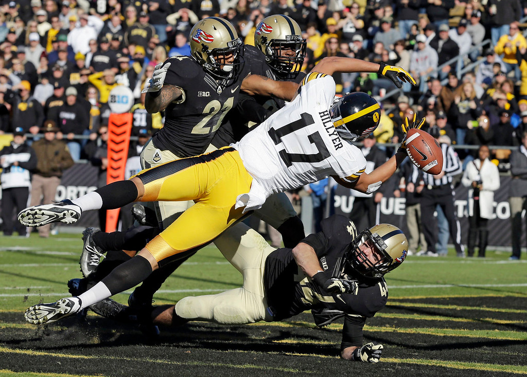 . Iowa wide receiver Jacob Hillyer (17) loses control of the ball in the end zone as he\'s surrounded by Purdue cornerback Ricardo Allen, top, left, defensive back Anthony Brown, top right, and safety Landon Feichter during the second half of an NCAA college football game in West Lafayette, Ind., Saturday, Nov. 9, 2013. Iowa defeated Purdue 38-14. (AP Photo/Michael Conroy)