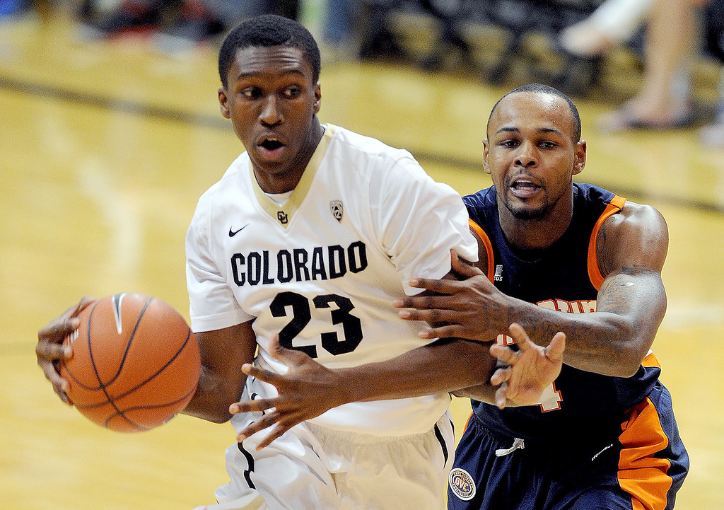 . Jaron Hopkins, of Colorado, drives past Bobby Jones, of Tenn-Martin, during the second half of the NCAA basketball game in Boulder, Colo., Sunday, Nov. 10, 2013. (The Daily Camera/Cliff Grassmick)