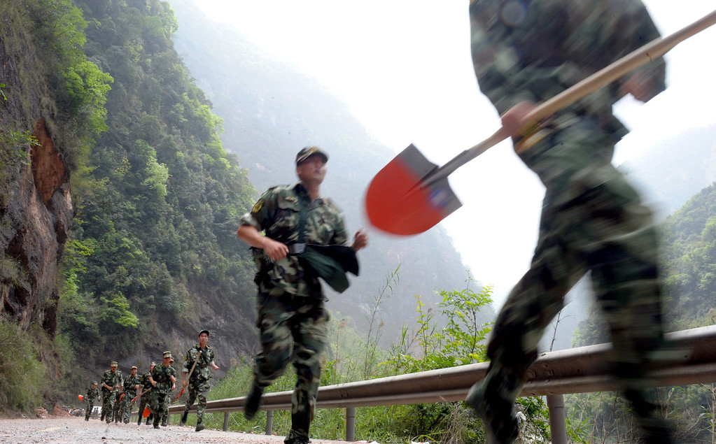 . This photo taken on April 21, 2013 shows rescuers running to clear up roads in disaster-hit Ya\'an, southwest China\'s Sichuan province.  STR/AFP/Getty Images