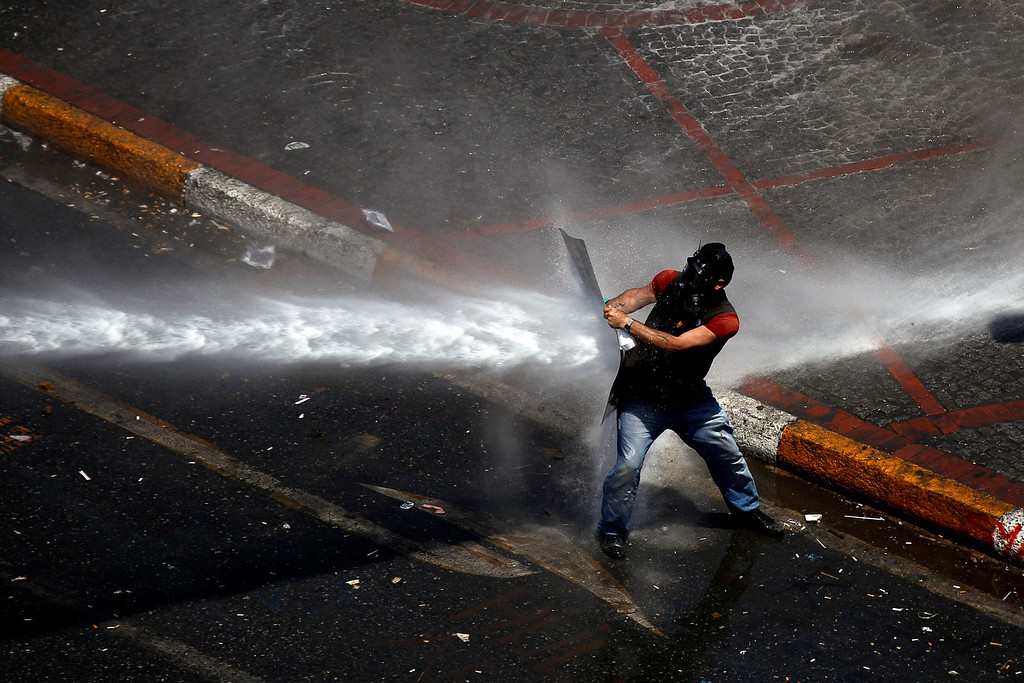 . A protester uses a makeshift shield to protect from water thrown by a canon from police   during clashes in Taksim square in Istanbul, Tuesday, June 11, 2013.  (AP Photo/Kostas Tsironis)