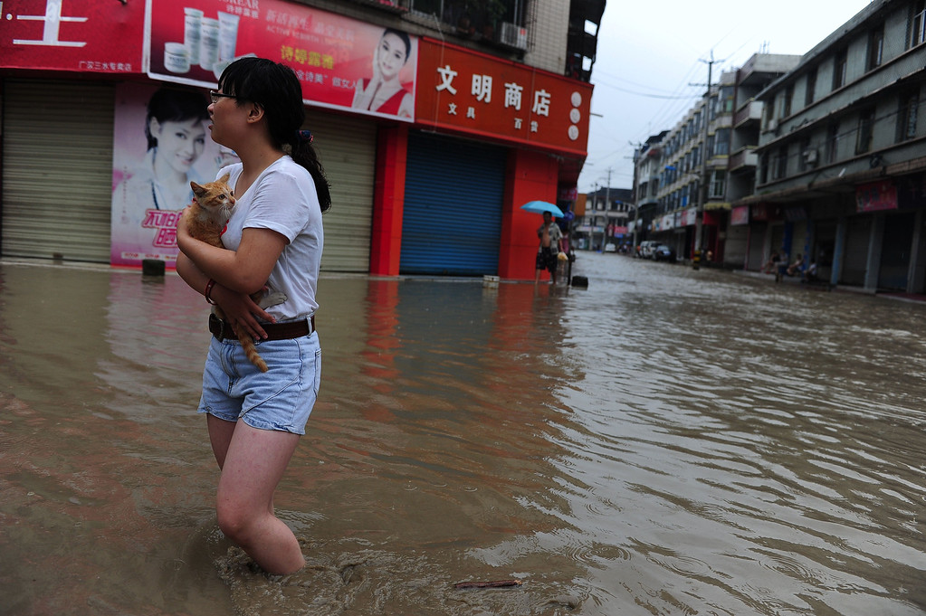 . Residents walk along a flooded street in a district in Guanghan, southwest China\'s Sichuan province. Rainstorms sweeping across parts of China have affected millions, causing landslides and disabling transportation in provinces such as Sichuan and Yunnan, state media reported.   AFP/AFP/Getty Images