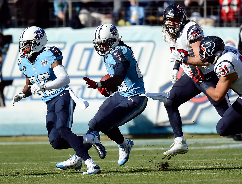 . Tennessee Titans running back Chris Johnson (28) follows the blocking of Nate Washington (85) as he carries the ball against Houston Texans defenders Brooks Reed (58) and Shiloh Keo (31) in the second quarter of an NFL football game Sunday, Dec. 29, 2013, in Nashville, Tenn. Johnson passed 1,000 yards rushing for the season on the play. (AP Photo/Mark Zaleski)