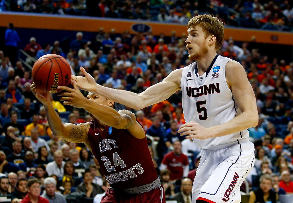 . BUFFALO, NY - MARCH 20: Chris Wilson #24 of the Saint Joseph\'s Hawks and Niels Giffey #5 of the Connecticut Huskies go for a loose ball during the second round of the 2014 NCAA Men\'s Basketball Tournament at the First Niagara Center on March 20, 2014 in Buffalo, New York.  (Photo by Jared Wickerham/Getty Images)