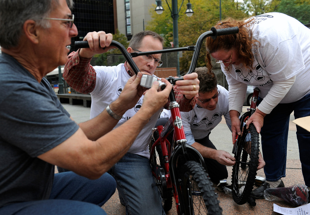 . DENVER, CO - Oct. 11: Assembling the bikes outside the Tabor Center downtown are left to right, Tom Iskiyan, Mike Hadden, Jim Wessels, and Julie Muhovich. Wish for Wheels and its volunteers build and give away over one hundred bikes to kindergarteners and first-graders at Smith Renaissance School in Park Hill. Wish for Wheels says its goal with one-in-five children liven in poverty, is to give as many kids as possible their first brand new bike and helmet. (Photo By Kathryn Scott Osler/The Denver Post)