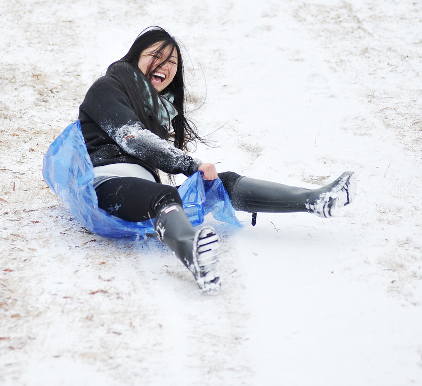 . University of Mississippi student Nancy Truong slides down a hill, in Oxford, Miss. on Tuesday, Feb. 10, 2014.  There is another chance of snow or sleet in northern Mississippi for Tuesday night, with low temperatures in the low to mid-twenties.  (AP Photo/Oxford Eagle, Bruce Newman)