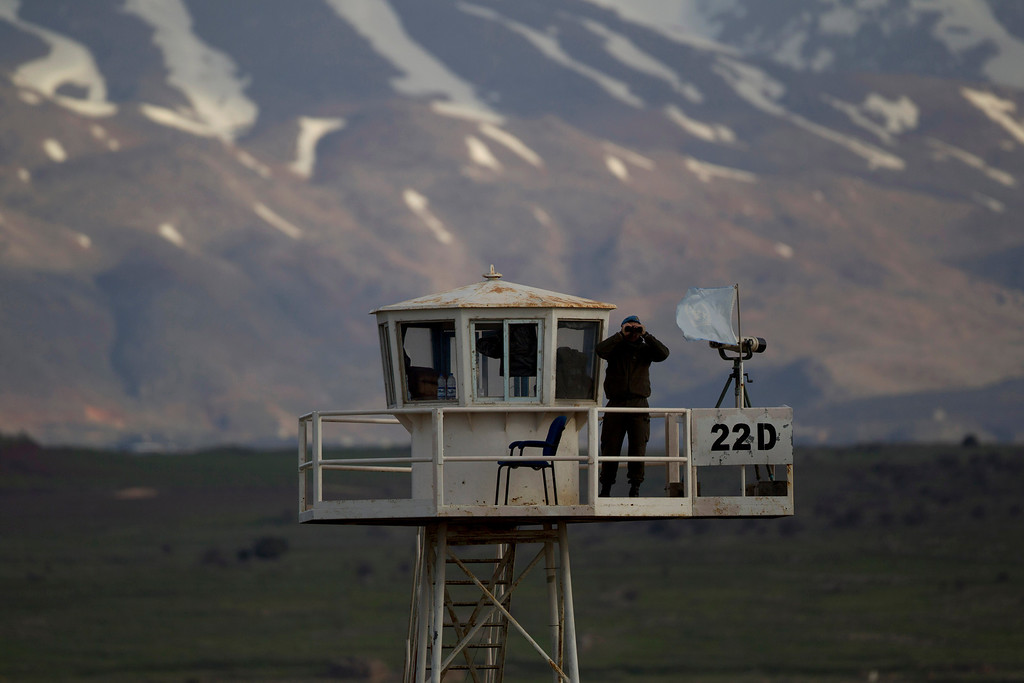 . A U.N. peacekeeper from the UNDOF force looks through binoculars as he guards on a watch tower at the Quneitra Crossing between Syria and the Israeli-controlled Golan Heights, Friday, March 8, 2013. Syrian rebels who seized 21 Filipino U.N. peacekeepers in the Golan Heights want the Red Cross to escort them out of the area because of fighting with Syrian government forces, the Philippine military said Friday. The 21 peacekeepers were seized Wednesday near the Syrian village of Jamlah, just a mile from the Israeli-controlled Golan Heights in an area where the U.N. force had patrolled a cease-fire line between Israel and Syria without incident for nearly four decades. (AP Photo/Ariel Schalit)