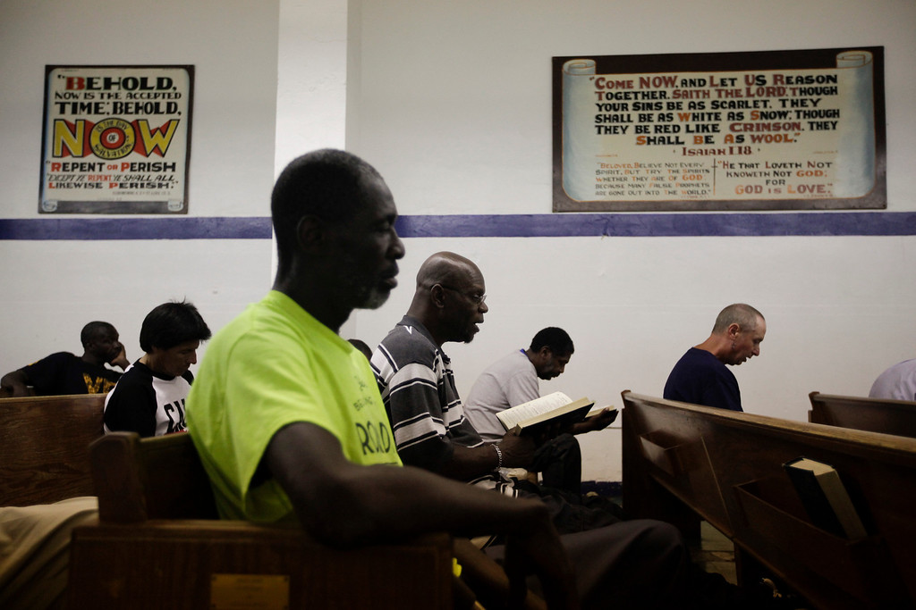 . Homeless people attend a daily Bible study class at the Emmanuel Baptist Rescue Mission in the Skid Row area of Los Angeles on Thursday, July 18, 2013. The church doubles as a shelter for homeless men and the Bible study attendance is required in order to get a bed assignment. (AP Photo/Jae C. Hong)