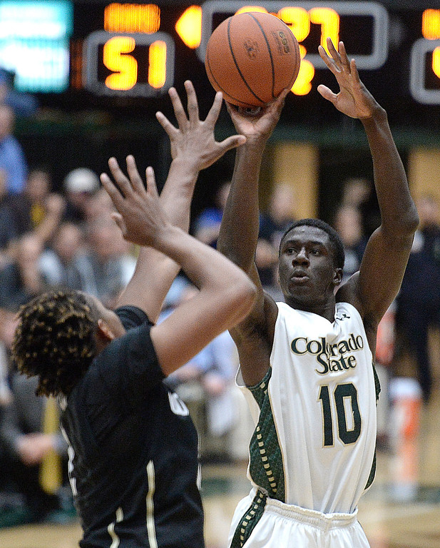 . CSU\'s Joe De Ciman takes a shot over Xavier Johnson during an NCAA game against CU on Tuesday, Dec. 3, 2013, at the Moby Arena in Fort Collins.
