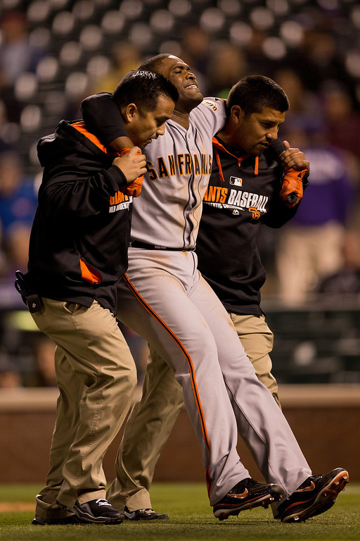 . Relief pitcher Santiago Casilla #46 of the San Francisco Giants is helped off the field after tripping over first base and injuring himself while running the bases during the ninth inning against the Colorado Rockies at Coors Field on May 21, 2014 in Denver, Colorado. The Giants defeated the Rockies 5-1. (Photo by Justin Edmonds/Getty Images)